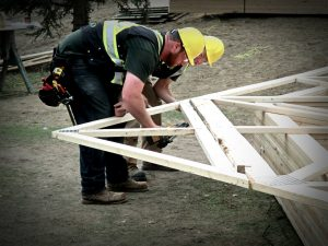 Construction workers preparing roof joists