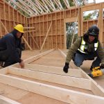 Framers assembling a large roof joist for large church roof