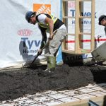 Two workers pouring and finishing concrete for c
